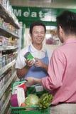 Försäljningar är kontorist att hjälpa mannen i supermarket, Peking arkivbilder