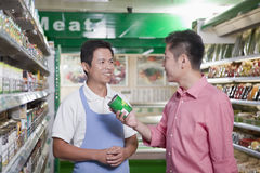 Försäljningar är kontorist att le och att hjälpa mannen i supermarket, Peking arkivbild