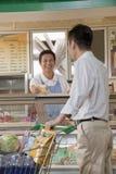 Försäljningar är kontorist att le, och hjälpa mannen på delikatessaffären kontra i supermarket fotografering för bildbyråer