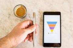 Försäljningar kanaliserar visat på en smart telefonskärm, den manliga handen som pekar på data arkivbilder