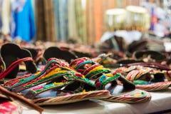 försäljningen av kulöra sandaler på afrikanen shoppar Arkivfoton