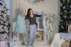 Försäljningen för kvinnashoppingjul väljer mellan blusgräsplan för två tröjor och gult lyckligt le på beige bakgrund arkivbilder