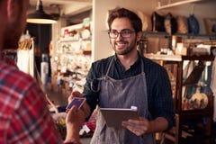 Försäljningsassistent med kreditkortavläsaren On Digital Tablet Arkivfoton