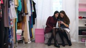 Försäljningsassistenten i portion för klädlager valde en ny klänning för kund genom att använda smartphonen och modetidskriften stock video