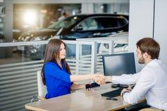 Försäljningschef och kvinnligkund som skakar händer som gratulerar sig på återförsäljarevisningslokalen arkivfoto