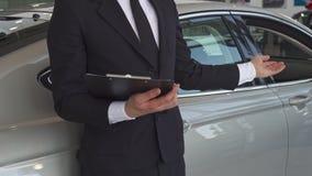 Försäljningschefen pekar hans hand på bilen royaltyfri foto