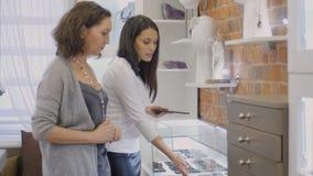 Försäljningschefen visar yewellery till den kvinnliga köparen i smyckenlager Arkivbilder