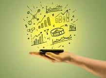 Försäljningsdiagram överst av mobiltelefonen i hand Arkivbild