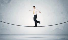 Försäljningsgrabb som balanserar på åtsittande rep arkivbilder
