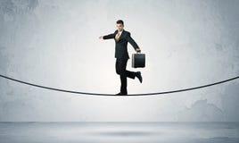 Försäljningsgrabb som balanserar på åtsittande rep arkivfoton