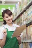 Försäljningskontorist Checking Groceries i supermarket arkivbild