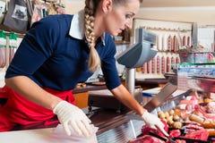 Försäljningskvinnan i slaktare shoppar sätta olika sorter av kött i skärm royaltyfria bilder