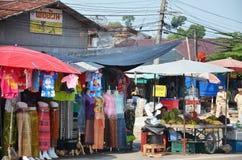 Försäljningsmat och kläder för thailändskt folk på den lilla marknaden Arkivfoto