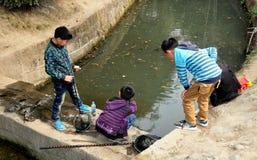 Pengzhou Kina: Pojkar som in fiskar, parkerar Arkivfoto