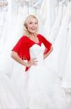 Försöka på en bröllopsklänning arkivfoto