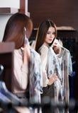 Försöka på en klänning och se i spegeln Arkivbild