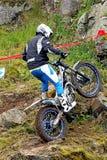 Försökmotorcykelryttare på stenig lutning med hjulsnurrandet Royaltyfria Bilder