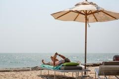 Försökta igen par som ligger på deckchairs genom att använda mobiltelefonen på stranden arkivbild