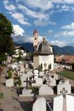 Församlingkyrka och kyrkogård i Dorf Tirol Arkivfoto