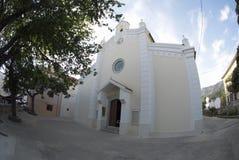 Församlingkyrkan av St-Treenighet och det gamla trädet i Baska på ön Krk, Kroatien arkivfoto
