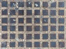 Förse med kloaker locket av fyrtioåtta metalliska fyrkanter för bakgrund arkivbild