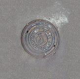 Förse med kloaker manhålräkningen som omges av en asfaltgata Arkivfoto