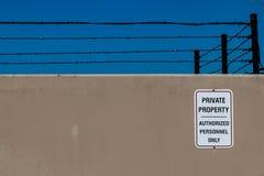 Försedd med en hulling betongvägg med ett tecken för privat egenskap och - tråd arkivbilder