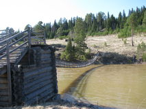 Försedd med gångjärn träbro över floden Royaltyfria Foton