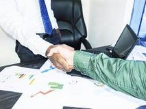Försegling av ett avtal Bästa sikt av två indiska män som sitter på skrivbordet och skakar händer arkivbilder