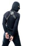Försening av en farlig terrorist i svartkläder och en maskering Arkivfoton