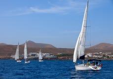 försett med besättning fyra segla fullt ut yachter Royaltyfri Fotografi