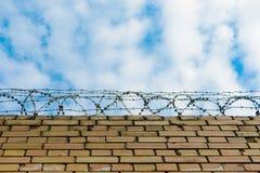 Försett med en hulling - binda på en tegelstenvägg mot en blå himmel med moln royaltyfri foto