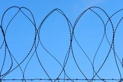 Försett med en hulling staket för säkerhet för rakknivtråd militärt Against Blue Sky arkivfoton