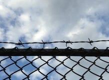 Försett med en hulling - staket för trådingrepp mot blå himmel Fotografering för Bildbyråer