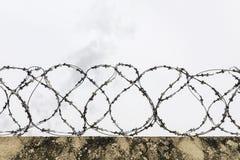 Försett med en hulling - tråd på ett konkret staket arkivfoto