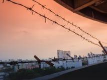 Försett med en hulling - trådstaket med skymninghimmel som ska kännas tyst och ensam och som önskas frihet Royaltyfri Foto
