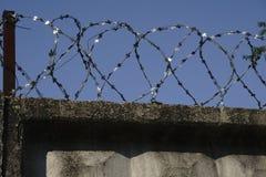 Försett med en hulling - trådstaket som fästas runt om fängelseväggar arkivfoton