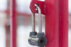 Försett med gångjärn metalllås på det röda gallerstaketet fotografering för bildbyråer