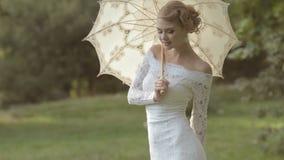 Försiktig brud med ett paraply på naturen arkivfilmer