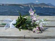 Försiktig bukett av små blommor på bakgrunden av havet Arkivbild