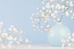 Försiktig elegant bukett av små blommor i keramisk cirkelbunke på mjuk pastellblåttbakgrund fotografering för bildbyråer