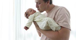 Försiktig fader med det nyfödda barnet på händer stock video