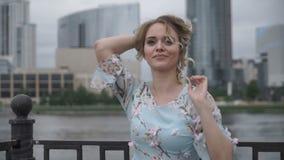 Försiktig flicka i klänning på cityscape lager videofilmer