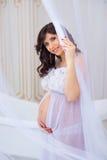 Försiktig havandeskap Härligt gravid i ljus vit klänning med orkidér Royaltyfri Fotografi
