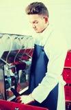 Försiktig manlig anställd som använder maskinen för att buteljera vin Royaltyfri Fotografi