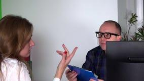 Försiktig manlig psykiaterman och besvärad kvinna psykologen noterar skrivplattan stock video