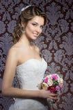 Försiktig stående av lyckliga le härliga sexiga flickor i den vita bröllopsklänningen med en bröllopbukett i hand med härligt hår Arkivfoton