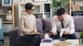 Försiktig terapeut som ger det pappers- silkespappret till att gråta affärsmannen som tröstar den upprivna mannen lager videofilmer