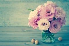 Försiktiga blommor i en glass vas med kopieringsutrymme - tappning fortfarande l Arkivfoto