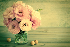 Försiktiga blommor i en glass vas med kopieringsutrymme - tonat retro arkivbild